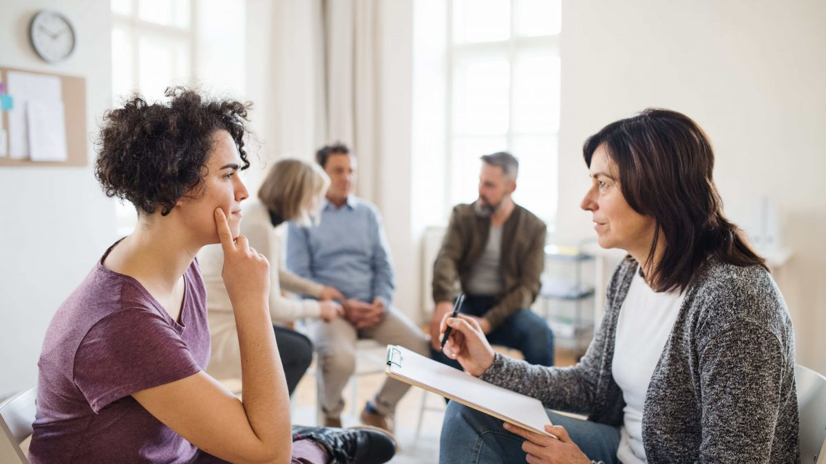 therapist talking to individual during group therapy
